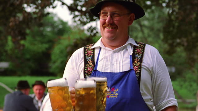 portrait man in german costume + apron holding three mugs of beer + smiling / bad kohlgrub, bavaria - german culture stock videos & royalty-free footage