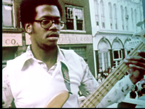 1976 montage man in glasses playing electric bass guitar. couple dancing / philadelphia, pennsylvania, usa - エレキギター点の映像素材/bロール