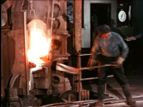 1946 man in goggles shoveling into furnace in factory / industrial - 1946 bildbanksvideor och videomaterial från bakom kulisserna