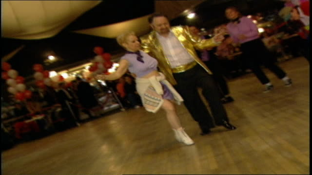man in gold jacket dancing with woman in purple at competition - 屋外遊具点の映像素材/bロール