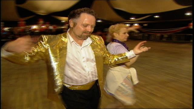 man in gold jacket dancing with woman in purple - 屋外遊具点の映像素材/bロール