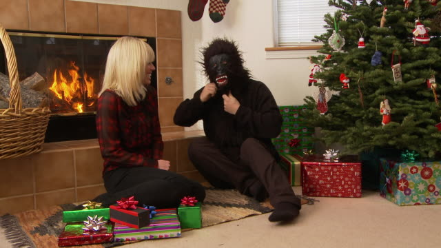 man in gorilla mask dances like a gorilla and then kisses woman near christmas tree / bellevue, idaho, united states - wide shot stock-videos und b-roll-filmmaterial