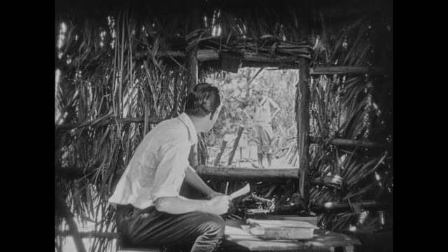 1925 man in grass hut drops pen in alligator infested water - grass hut stock videos & royalty-free footage