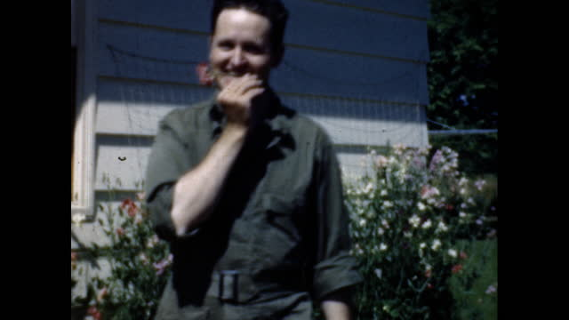 man in green jumpsuit bends over to pick a flower off of a bush in front yard of a home - postwar stock videos & royalty-free footage
