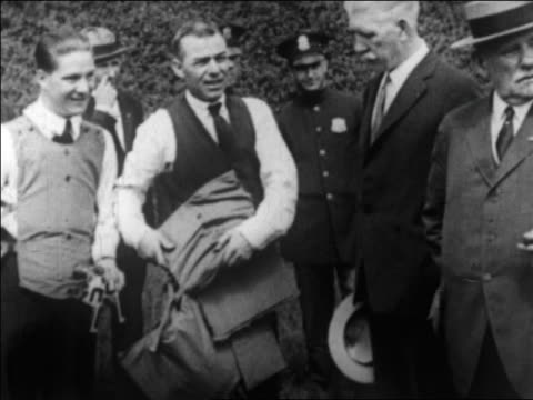 vídeos de stock, filmes e b-roll de b/w 1922 man in group holding bullet-proof vest outdoors / newsreel - vest