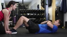 Man In Gym Doing Sit Ups Encouraged By Personal Trainer