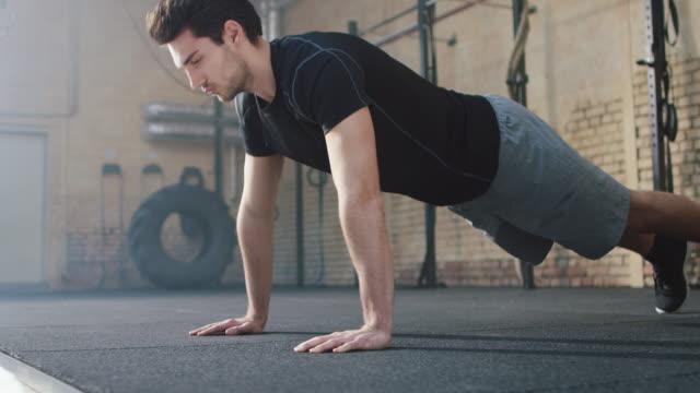 vídeos de stock e filmes b-roll de homem no ginásio fazendo flexões de braços - flexão de braço