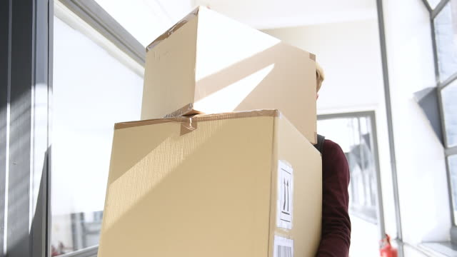 man in hallway carrying cardboard boxes - moving office stock videos & royalty-free footage