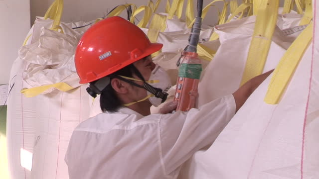MS Man in hardhat and facemask hooks large bag to pulley lifter in factory / Kunshan, China