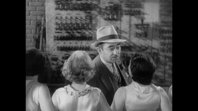 1931 man in hat asks line of dancing girls whereabouts of missing reporter - 1931 stock videos & royalty-free footage