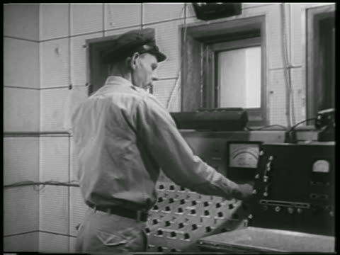 man in hat at control panel in mission control for rocket carrying animals / white sands - 1952 stock-videos und b-roll-filmmaterial