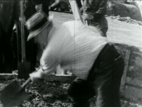 b/w 1934 man in hat laying cement with shovel on hillside in wpa construction project / documentary - anno 1934 video stock e b–roll