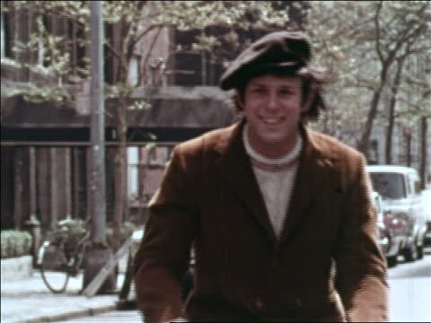 1969 man in hat riding bicycle toward camera on city street / greenwich village, nyc - 1969 bildbanksvideor och videomaterial från bakom kulisserna