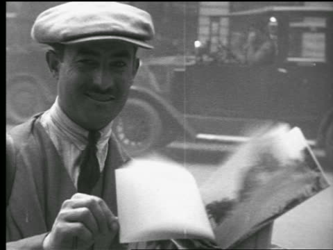 B/W 1927 PORTRAIT man in hat smiling + flipping through photo book of monuments / cars in background / Paris