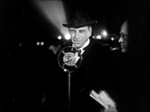b/w 1928 man in hat talking into microphone at interference premiere / starlet nearby / newsreel - 1928年点の映像素材/bロール