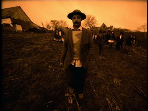 sepia man in hat walking toward camera in field / others in native dress in background / sibiu, transylvania - transylvania stock-videos und b-roll-filmmaterial