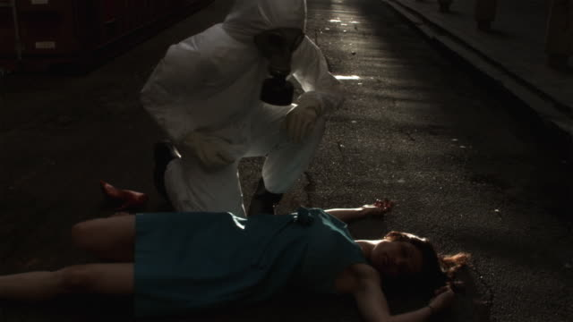 SLO MO MS Man in HAZMAT suit examining unconscious woman lying on road, Atlanta, Georgia, USA