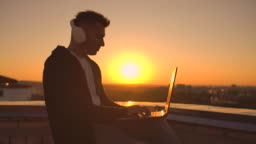 A man in headphones on the roof relaxes working remotely enjoying life despite a handsome kind of sipping beer and types on the keyboard.