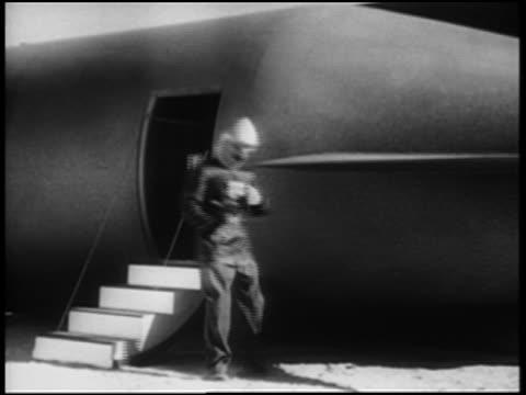 b/w 1952 man in helmet + jet pack walking away from spaceship, turning on jet pack + taking off - actor stock videos & royalty-free footage