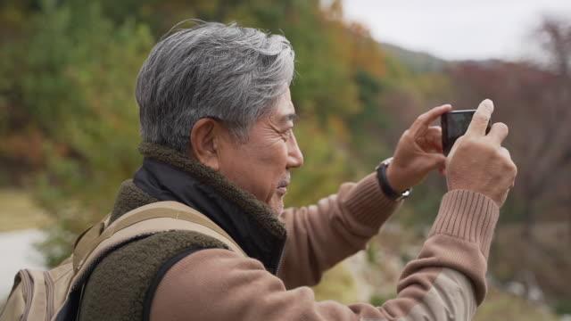 a man in his 60s taking photos by mobile phone / yangpyeong-gun, gyeonggi-do, south korea - human nose stock videos & royalty-free footage