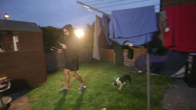 vídeos y material grabado en eventos de stock de man in his back garden is going to cook bbq - cuerda de tender la ropa