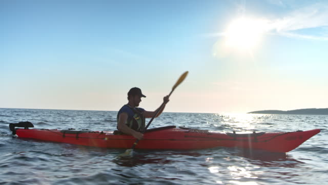 vídeos de stock e filmes b-roll de slo mo ts man in his kayak gliding across the sea - barco