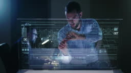 A man in his own studio uses a glass monitor with holography to design, navigate and build.