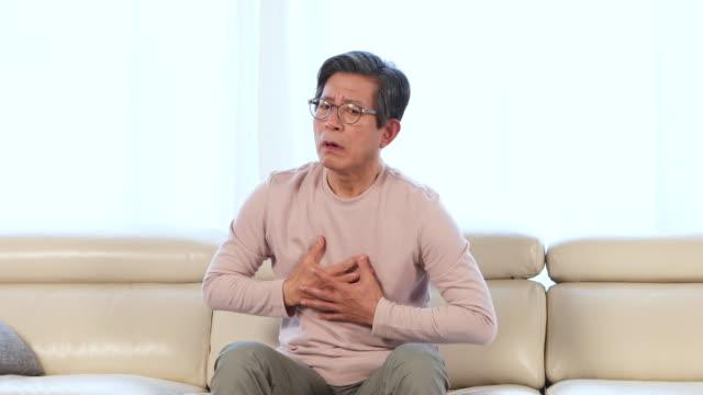 vídeos de stock e filmes b-roll de man in his sixties having a pain in chest - asmático