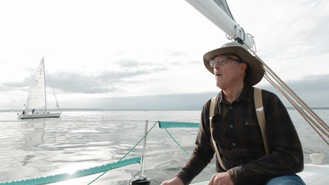 a man in his sixties pulls a rope tight in a winch on his sailboat on the puget sound in washington while his crew sits on the deck looking at the view - team captain stock videos & royalty-free footage