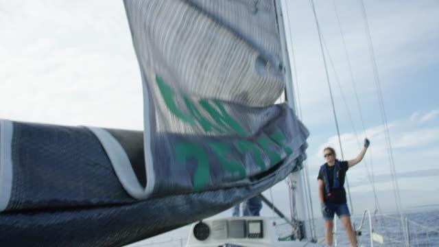 vidéos et rushes de un homme dans ses années soixante montres que son équipage hoists la voile d'un voilier à puget sound près de seattle, washington - équipe de voile