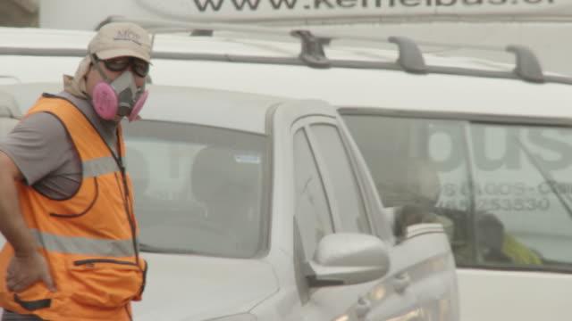 ensenada, chile - april 26, 2015: man in hi-viz vest, people in dust masks walk along road - ash stock videos & royalty-free footage
