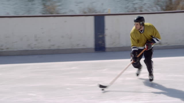 ws pan man in hockey uniform skating on ice rink, pushing puck around with hockey stick/ long island, ny - hockey glove stock videos & royalty-free footage