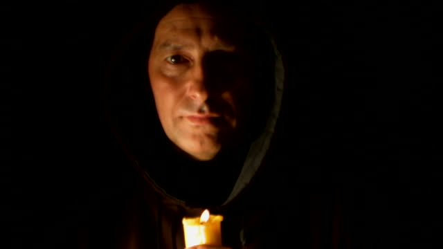 Man in hood with candle