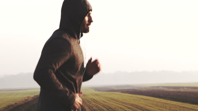 slo mo man in hooded sweatshirt jogging in countryside at dawn - side view stock videos & royalty-free footage