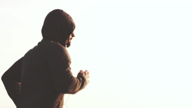 vídeos de stock e filmes b-roll de slo mo man in hooded sweatshirt jogging in the morning - sweatshirt