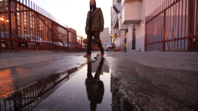 Man in Hoodie Walking Through Puddle