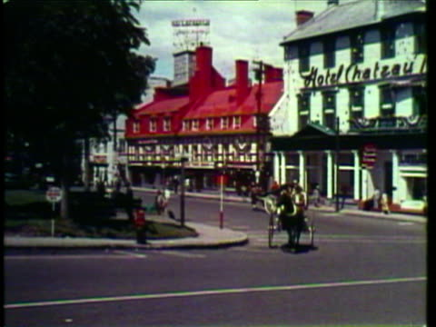 1953 ws pan man in horse drawn carriage trots in front of hotel chateau and underneath bridge / ottawa, ontario, canada / audio - ottawa stock videos & royalty-free footage