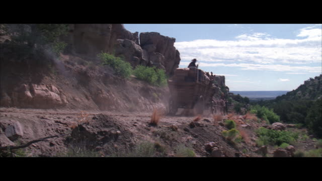 ms, pan reenactment man in horse-drawn wagon and horseback riders shooting guns on mountain road - horsedrawn stock videos and b-roll footage