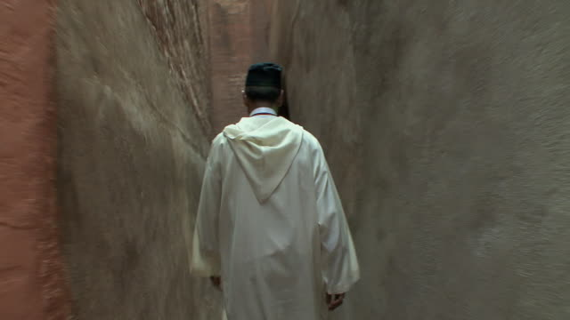 stockvideo's en b-roll-footage met ms pov man in jellaba walking through narrow alleyways, marrakech, morocco - oude stad
