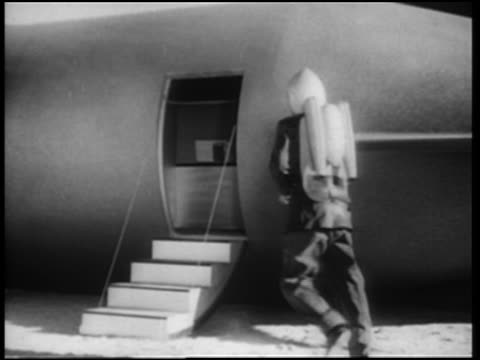 b/w 1952 rear view man in jet pack entering spaceship + door closing behind him - space exploration stock videos & royalty-free footage