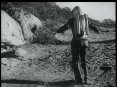 b/w 1952 man in jet pack lands on ground + runs away around large rock - 1952 stock videos & royalty-free footage