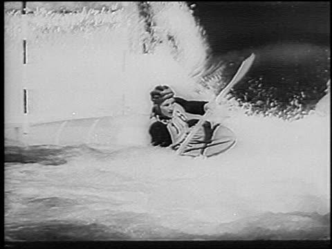 b/w 1966 man in kayak steering around poles in slalom competition on rapids / germany / newsreel - 若い男性だけ点の映像素材/bロール