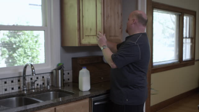 vídeos de stock, filmes e b-roll de man in kitchen getting milk from fridge and pouring a glass of it to drink. - cabinet