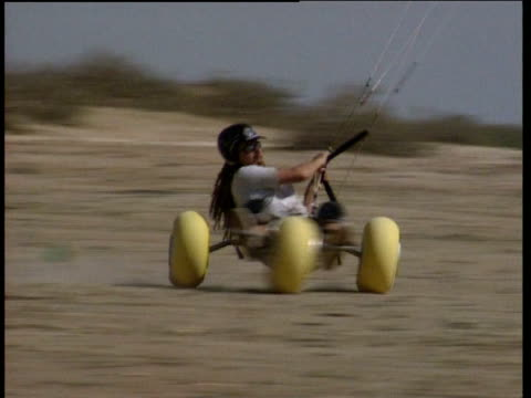 Man in Kite buggy twists on sand