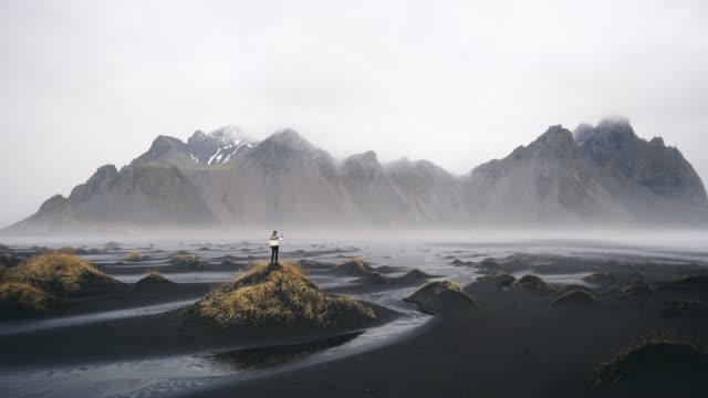 man in knitted sweater looking at vestrahorn mountains near the sea - mountain range stock videos & royalty-free footage