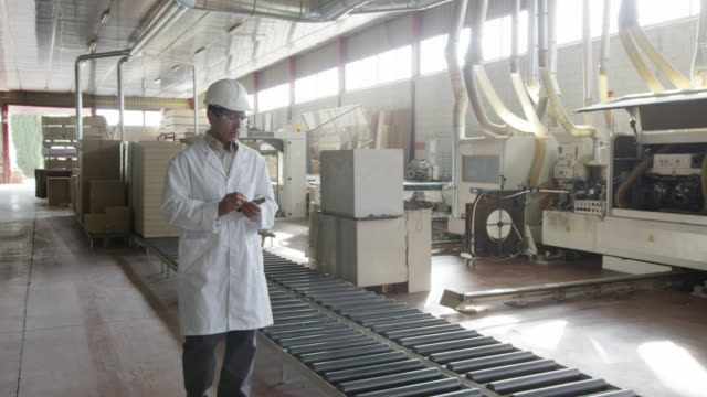 WS TS man in lab coat and hard hat walking along furniture production line, taking notes on handheld electronic device
