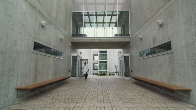 ws ms man in lab coat exiting building, talking on phone, squamish, british columbia, canada - coat stock videos & royalty-free footage