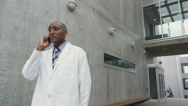 DS MS LA Man in lab coat talking on phone outside building, Squamish, British Columbia, Canada