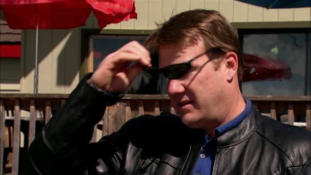 cu portrait man in leather jacket removing sunglasses in front of restaurant/ fresno county, california - leather jacket stock videos and b-roll footage