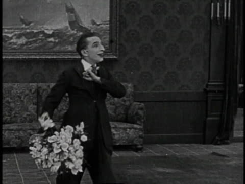 1920 montage man in living room holding bouquet of flowers calling for his darling and then running toward her reflection in a large mirror - bunches stock videos & royalty-free footage